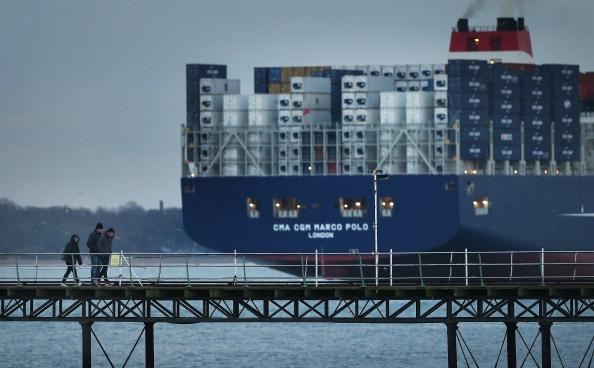 SOUTHAMPTON, ENGLAND - DECEMBER 10:  People walk on a pier at Hythe as The Marco Polo, the world's biggest container ship, leaves Southampton on December 10, 2012 in England.  On its first visit to Europe, the 54m (177ft) wide and 396m (1299ft) long container ship - which is 51m (167ft) longer than the Queen Mary II - will mostly carry consumer goods for delivery to shops for Christmas.  (Photo by Peter Macdiarmid/Getty Images)