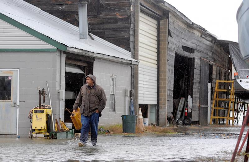 Chris Scarlato of Havre de Grace, Md., carries a gas can in a flooded marina yard in Havre de Grace as the aftermath of superstorm Sandy continues to disrupt routines on the East Coast Tuesday, Oct. 30, 2012. (AP Photo/Steve Ruark)