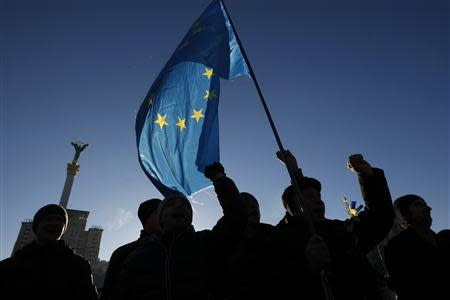 Protesters wave flags and shout slogans on Independence Square in Kiev