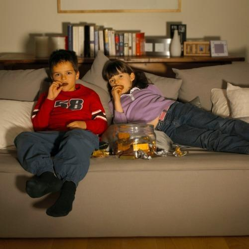 Kids on a couch eating snacks and watching a screen