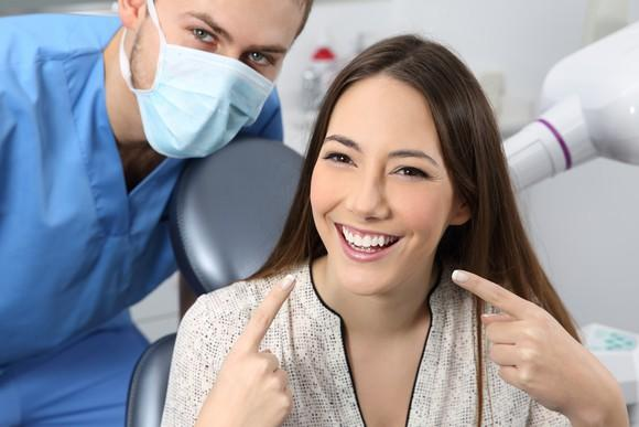 Dentist posing with smiling patient pointing to white teeth