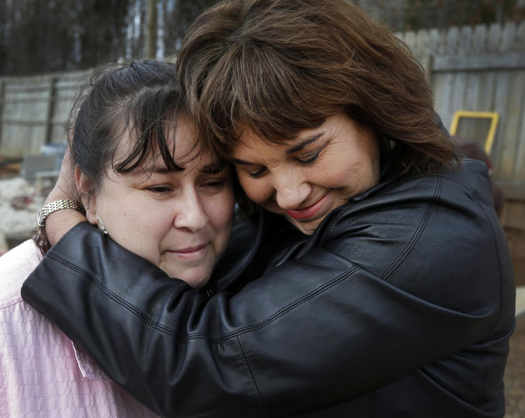 In this Feb. 28, 2013 photo, Sarah Chavez, left, is embraced by Caron Myers at her home in Lexington, N.C. Desperate to raise money for their 6-year-old daughter's cancer treatments last summer, friends told Jose and Sarah Chavez of a way to quickly turn their meager savings into a small fortune. But what the Chavez family and many others didn't know was that state and federal regulators for months had received complaints that ZeekRewards was a scam. (AP Photo/Chuck Burton)