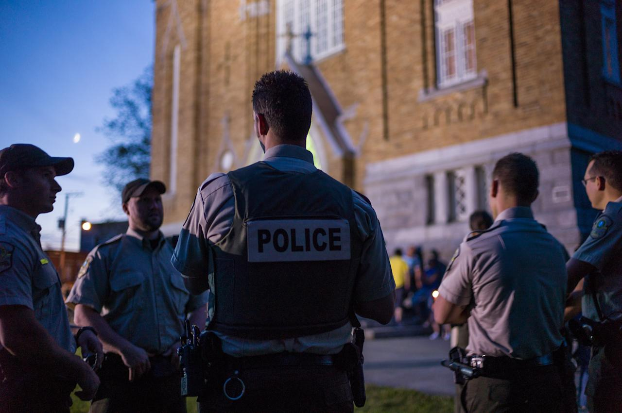 LAC-MEGANTIC, CANADA - JULY 12: Police watch over a public vigil at the Presbyteres-Eglises July 12, 2013 in Lac-Megantic, Quebec, Canada. A train derailed and exploded into a massive fire that flattened dozens of buildings in the town's historic district, leaving 60 people dead or missing in the early morning hours of July 6. (Photo by Ian Willms/Getty Images)