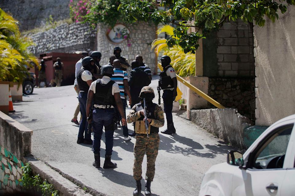 Security forces conduct an investigation as a soldier stands guard at the entrance to the residence of Haitian President Jovenel Moise, in Port-au-Prince, Haiti. (AP)