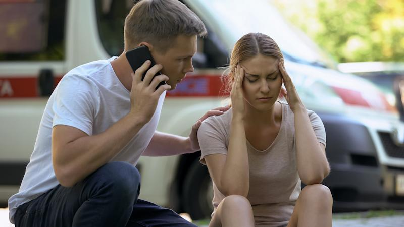 Female suffering headache, not indifferent man calling ambulance, first aid