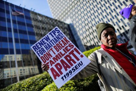 A woman holds a placard as Haitian immigrants and supporters rally to reject DHS Decision to terminate TPS for Haitians, at the Manhattan borough in New York, U.S., November 21, 2017.  REUTERS/Eduardo Munoz