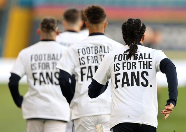 Leeds United players wearing 'Football Is For The Fans' shirts during the warm up to their match against Liverpool
