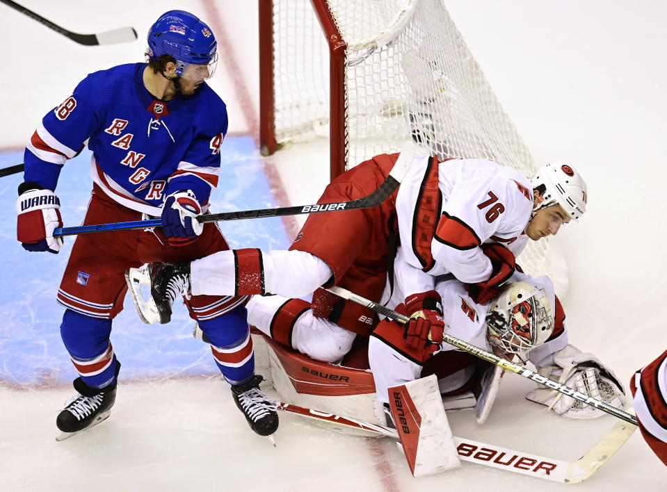 Carolina Hurricanes' Brady Skjei (76) falls on to his goaltender James Reimer (47) as New York Rangers' Brendan Lemieux (48) looks on during second period NHL Eastern Conference Stanley Cup playoff action in Toronto on Tuesday, Aug. 4, 2020. (Frank Gunn/The Canadian Press via AP)