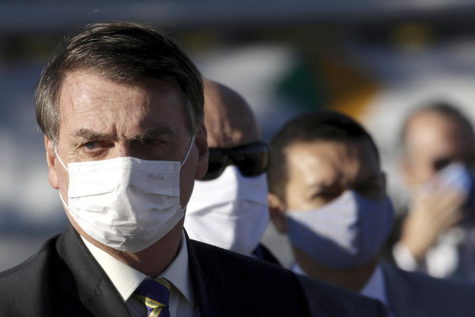 Brazil's President Jair Bolsonaro arrives for a flag raising ceremony outside Alvorada palace, the presidential residence in Brasilia, Brazil, Tuesday, May 12, 2020. The morning ceremony flew Brazil's flag at half mast to mourn those who have died from the new coronavirus. (AP Photo/Eraldo Peres)