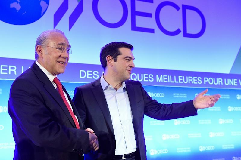 OECD Secretary General Angel Gurria (L) shakes hand with Greek Prime Minister Alexis Tsipras during Tsipras' visit to the OECD headquarters in Paris, March 12, 2015