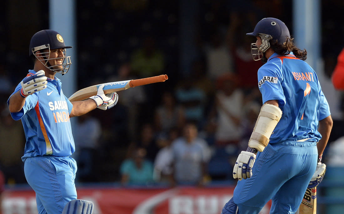 Indian cricket team captain Mahendra Sing Dhoni (L) celebrates with teammate Ishant Sharma after hitting a boundary for six runs to seal their victory during the final match of the Tri-Nation series between India and Sri Lanka at the Queen's Park Oval stadium in Port of Spain on July 11, 2013. India defeated Sri Lanka by 1 wicket to win the series. AFP PHOTO/Jewel Samad