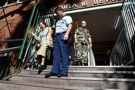 A police officer helps a woman go down the stairs after she voted in the presidential election at Buenos Aires, Argentina, November 22, 2015. REUTERS/Ivan Alvarado