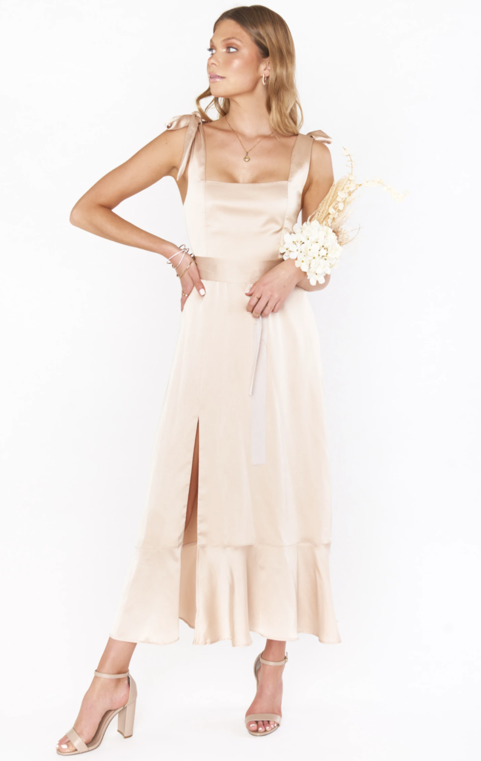 blone model posing with hand on hip in nude silk bridesmaids dress holding bouquet of flowers