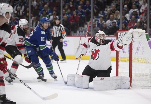 New Jersey Devils goalie MacKenzie Blackwood, right, makes a glove-save as Devils' Kyle Palmieri (21) and Vancouver Canucks' Jay Beagle (83) watch during the second period of an NHL hockey game in Vancouver, British Columbia, Sunday, Nov. 10, 2019. (Darryl Dyck/The Canadian Press via AP)