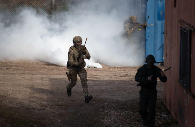 Royal Marine Commandos storm a compound during a live exercise demonstration at Bovington Camp in Dorset to showcases core equipment capabilities highlighted in Monday's defence command paper