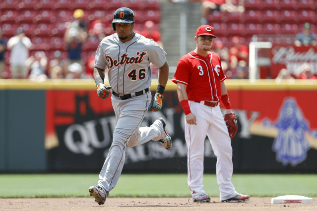 Detroit Tigers' Jeimer Candelario (46) runs the bases past Cincinnati Reds second baseman Scooter Gennett (3) after hitting a solo home run off starting pitcher Tyler Mahle in the first inning of a baseball game, Wednesday, June 20, 2018, in Cincinnati. (AP Photo/John Minchillo)
