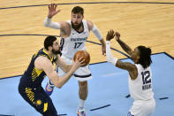 Indiana Pacers center Goga Bitadze, left, shoots against Memphis Grizzlies guard Ja Morant (12) and center Jonas Valanciunas (17) in the second half of an NBA basketball game Sunday, April 11, 2021, in Memphis, Tenn. (AP Photo/Brandon Dill)