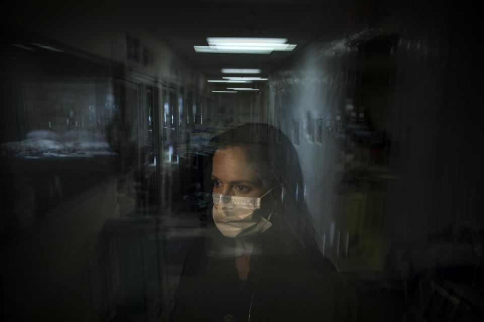 """In this photo created with an in-camera multiple exposure, registered nurse Lisa Lampkin, part of a group of nurses who had been treating coronavirus patients in an intensive care unit, stands for a portrait in the empty COVID-19 ICU at Providence Mission Hospital in Mission Viejo, Calif., Tuesday, April 6, 2021. """"I would go home, try to sleep,"""" she says. Then she would """"wake up to the reality of this pandemic again."""" (AP Photo/Jae C. Hong)"""