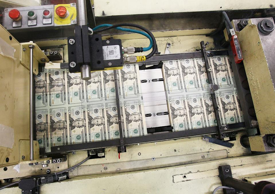Stacks of twenty dollar bills pass through on machine at the Bureau of Engraving and Printing. (Photo: Mark Wilson/Getty Images)