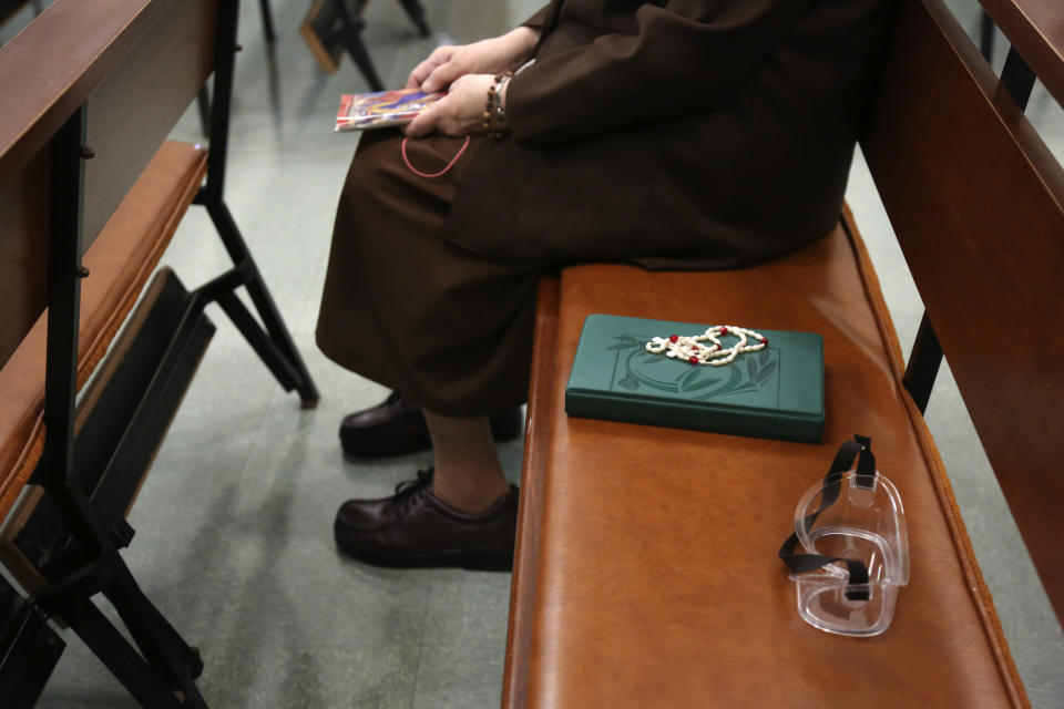 Sister Mary Carol Kardell, of the Felician Sisters of North America, sits beside a Bible, rosary beads and goggles during morning Mass at St. Anne Home in Greensburg, Pa., on Thursday, March 25, 2021. Last October the nuns lost one of their own, Sister Mary Evelyn Labik, to the coronavirus. (AP Photo/Jessie Wardarski)