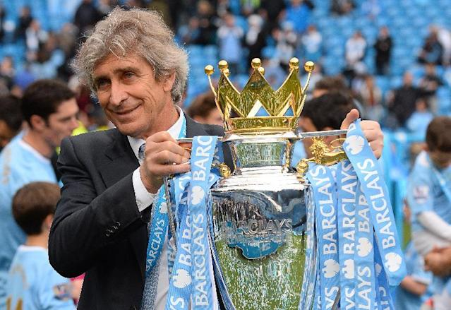 Manchester City's Chilean manager Manuel Pellegrini poses for pictures with the Premier League trophy at the Etihad Stadium in Manchester on May 11, 2014 (AFP Photo/Andrew Yates)