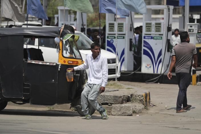 A physically disabled Kashmiri man waits for transport after buying fuel from a fuel station in Srinagar, India, Sunday, Aug. 4, 2019. People in Srinagar and other towns in Indian kashmir thronged grocery stores and medical shops to stock up on essentials. Tensions have soared along the volatile, highly militarized frontier between India and Pakistan in the disputed Himalayan region of Kashmir as India deployed more troops and ordered thousands of visitors out of the region. (AP Photo/Mukhtar Khan)