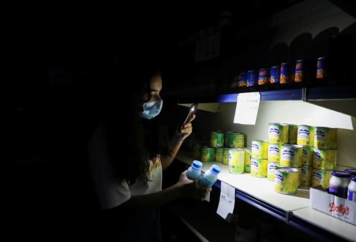 A customer uses her phone's torch light in a grocery store during a power cut near Bhamdoun