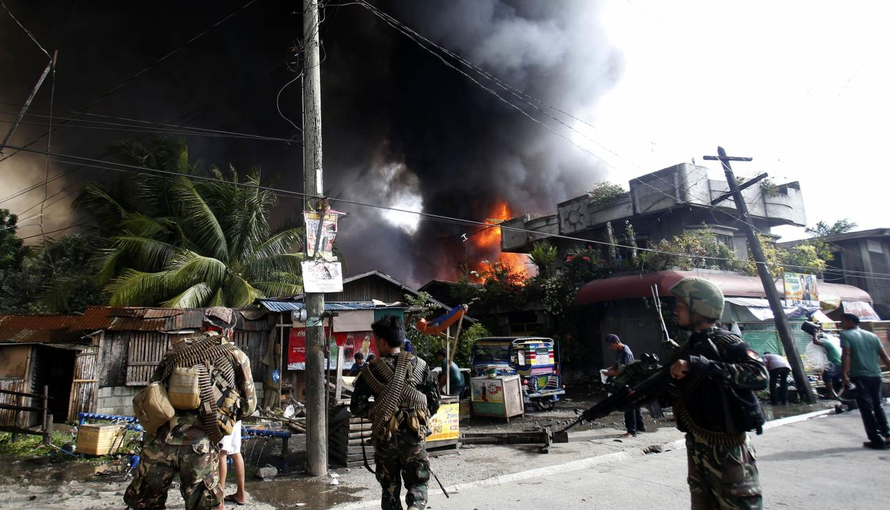 Government soldiers secure a street as fire spreads in a residential neighbourhood after a firefight with Muslim rebels from the Moro National Liberation Front (MNLF) in Zamboanga city, in southern Philippines, September 12, 2013. Fighting between security forces and the rogue Muslim rebels seeking to declare an independent state escalated in Zamboanga city on Thursday and spread to a second island, officials said. U.S.-trained commandos exchanged gunfire with a breakaway faction of the MNLF holding dozens of hostages in Zamboanga City, on the southernmost island of Mindanao, army spokesman Domingo Tutaan said. REUTERS/Erik De Castro (PHILIPPINES - Tags: CIVIL UNREST CONFLICT POLITICS)