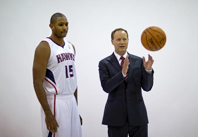 Atlanta Hawks head coach Mike Budenholzer, right, is tossed a basketball by a photographer before posing for a photo with Al Horford, left, during the team's NBA basketball media day, Monday, Sept. 30, 2013, in Atlanta. (AP Photo/David Goldman)