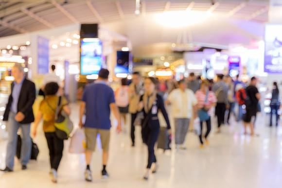 Passengers walking through an airport boarding area; blurred photographic effect.