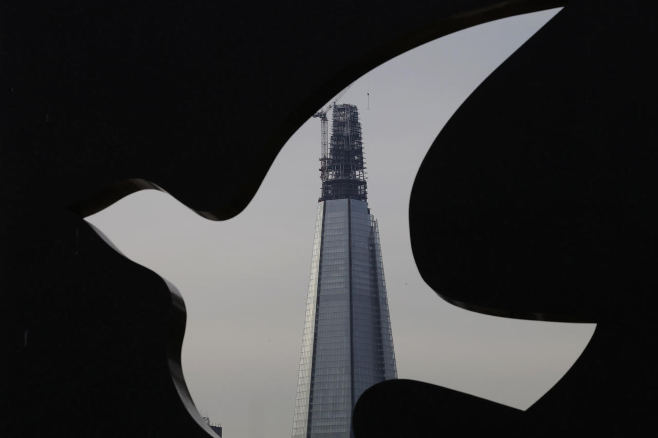 A view of The Shard, a newly-constructed high-rise building in London, seen through an outdoor art installation, Tuesday, Jan. 17, 2012. Passengers stepping out of London Bridge station cannot help but crane their necks to gaze at the jagged tower under construction: The Shard is the tallest building in the European Union and looks like a slice of glass balanced on the edge of the financial district. When the tower opens next year, visitors to the observation deck will see helicopters fly by at eye level and take in the metropolis all the way to the distant north Downs Hills. The structure designed by renowned Italian architect Renzo Piano dwarfs nearby landmarks like Tower Bridge and St. Paul's Cathedral . (AP Photo/Lefteris Pitarakis)