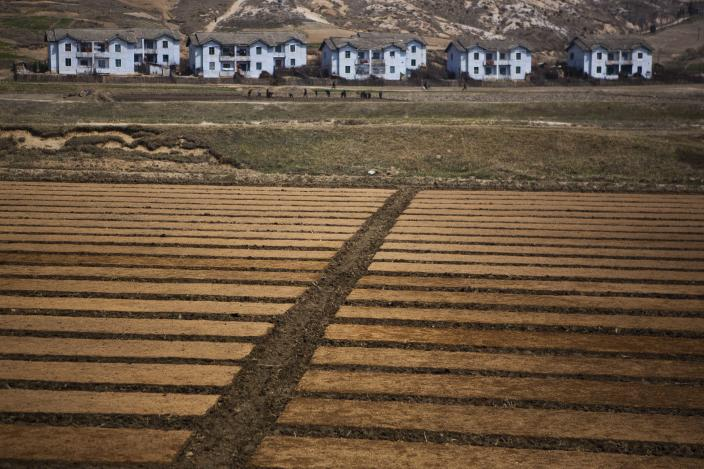 In this April 24, 2013 photo, North Korean fields stretch out before housing blocks north of Kaesong, North Korea. (AP Photo/David Guttenfelder)