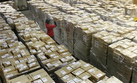 A worker checks a shipment of boxes at the Amazon.com warehouse facility in New Castle Delaware