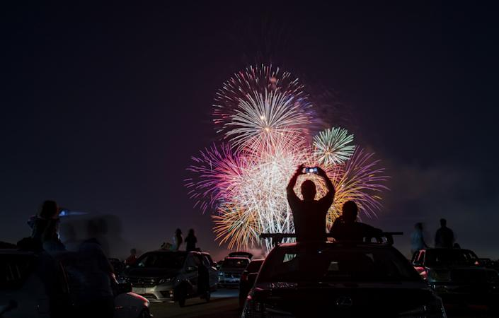 People sit atop their cars, holding up cellphones to take photos and video, as multiple fireworks explode.
