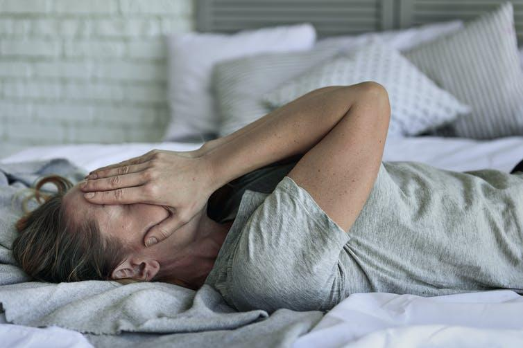 A woman with long COVID lying on a bed, covering her face