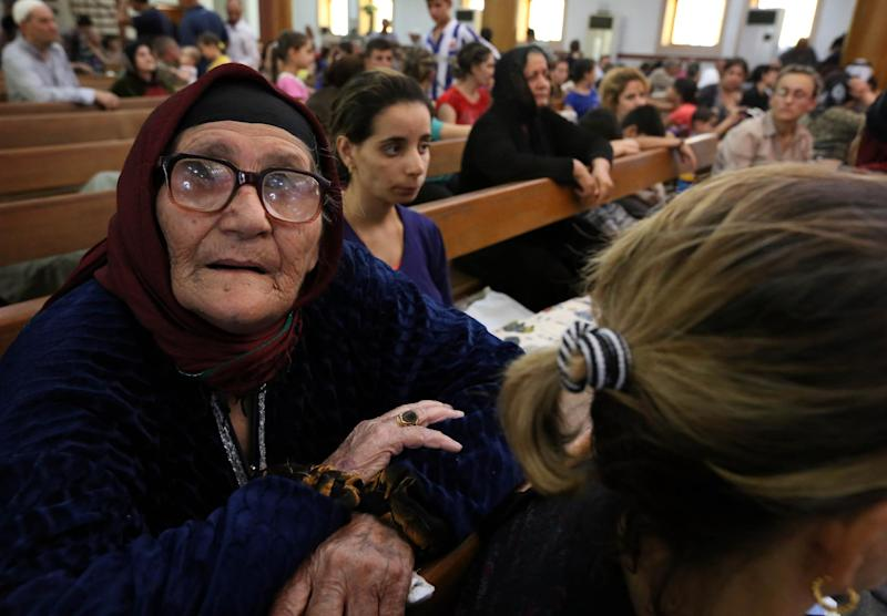 Iraqi Christians who fled the violence in the village of Qaraqush, about 30 kilometres east of the northern province of Nineveh, rest upon their arrival at Saint-Joseph's church in the Kurdish city of Arbil, on August 7, 2014 (AFP Photo/Safin Hamed)