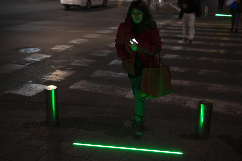 In this Wednesday, March 13, 2019 photo, An Israeli woman walks past embedded LED stoplights at a crosswalk in Tel Aviv, Israel. Tel Aviv has taken its first steps to assist pedestrians distracted by their smartphones by embedding LED stoplights at crosswalks. (AP Photo/Sebastian Scheiner)