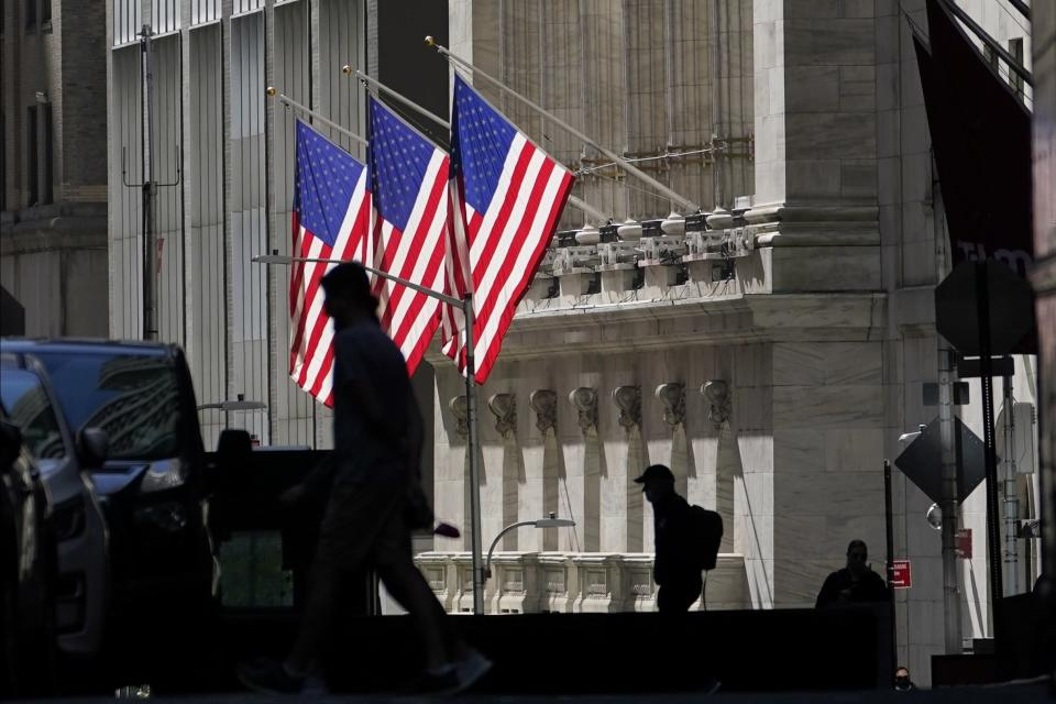FILE - In this Oct. 14, 2020 file photo, pedestrians pass the New York Stock Exchange in New York. Shares are opening mostly lower on Wall Street, Wednesday, March 17, 2021, as investors cautiously await the U.S. central bank's latest assessment on the economy. (AP Photo/Frank Franklin II, File)