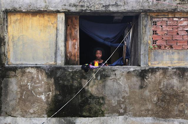 <p>Agatha, 13, stands in the window of her family's home in the Mangueira favela, May 2, 2017, in Rio de Janeiro. (Photo: Mario Tama/Getty Images) </p>
