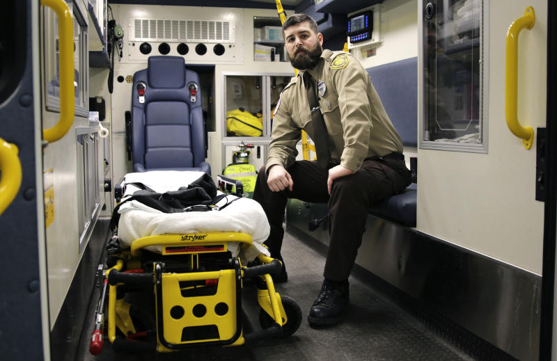In this Thursday, March 20, 2014 photo, Boston Emergency Medical Services EMT Paul Mitchell sits in an ambulance at his station in the Hyde Park neighborhood of Boston. Mitchell, with bystander Carlos Arredondo and volunteer Devin Wang, are credited with helping to save the life of Jeff Bauman, who suffered traumatic injuries in the Boston Marathon bombings. (AP Photo/Charles Krupa)