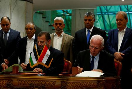 Head of Hamas delegation Saleh Arouri and Fatah leader Azzam Ahmad sign a reconciliation deal in Cairo, Egypt, October 12, 2017. REUTERS/Amr Abdallah Dalsh