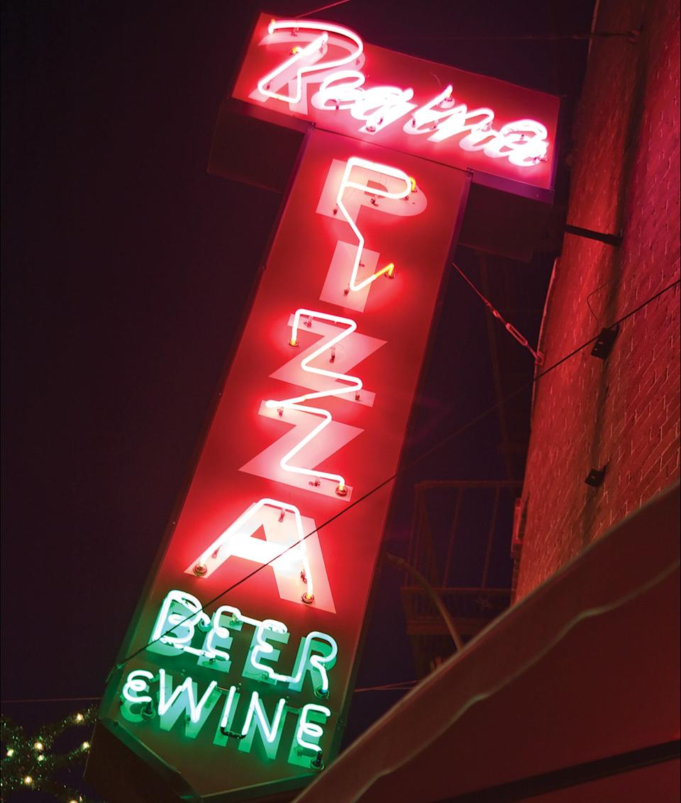 <p><strong>Start us off with an overview.</strong></p> <p>Everyone in Massachusetts has heard of Regina's, and their original pizzeria serves the broken-in charm that extends to its local empire of counter-service locations. Celebrity photos and police badges from visitors adorn walls split by mustard-yellow paint and dark-wood paneling. On red formica tables, worn by the consistent sliding of aluminum pizza pans, everything is branded, from the root beer to the napkins.</p> <p><strong>What's the crowd like?</strong></p> <p>Tourists may flock to Regina's, but this is a New England joint through and through. Fans from near and far duck into the original before a sports game or after a weekend stroll. People are relieved to see the Polcari family's longtime establishment still standing after its parent company filed Chapter 11 bankruptcy a few years ago.</p> <p><strong>What should we be drinking?</strong></p> <p>Draft beers are the norm here, and nothing fancy, though there's wine on the menu, too.</p> <p><strong>Main event: the food. Give us the lowdown—especially what not to miss.</strong></p> <p>Crispy dough, spiced sauce, and salty cheese make a satisfying symphony at Regina's, where thin-crust pizzas roll out of the kitchen like clockwork. Dig into a classic Giambotta pizza—piled with pepperoni, sausage, salami, mushrooms, peppers, onions, fresh basil, and mozzarella cheese (plus anchovies if you want them). If that's too much, order a few small pies, with just a topping or two, or even a classic margherita. Don't expect salads or pastas here; this is a pizza-only joint.</p> <p><strong>And how did the front-of-house folks treat you?</strong></p> <p>Regina's team members can be no-nonsense, but they're true to the soul of the place. They keep the chaos of the institution (and its out-the-door line) at bay.</p> <p><strong>What's the real-real on why we're coming here?</strong></p> <p>Regina's is ideal for family meals over greasy pies. If you're not up for the wait