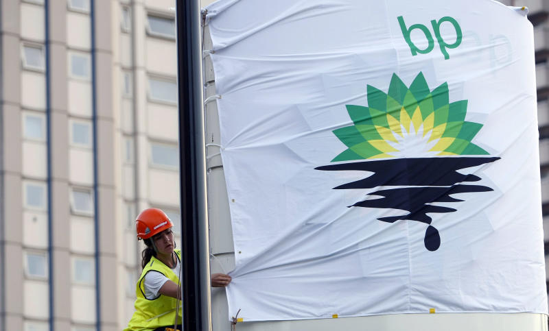 FILE-In this Tuesday, July 27, 2010, file photo, a Greenpeace activist puts up a banner as they block off a British Petroleum fuel station in protest as the BP board announce their annual results, in London. A BP executive has been indicted on charges that he lied to authorities about his work estimating the rate oil was flowing during the 2010 Gulf oil spill disaster. (AP Photo/Alastair Grant, FIle)