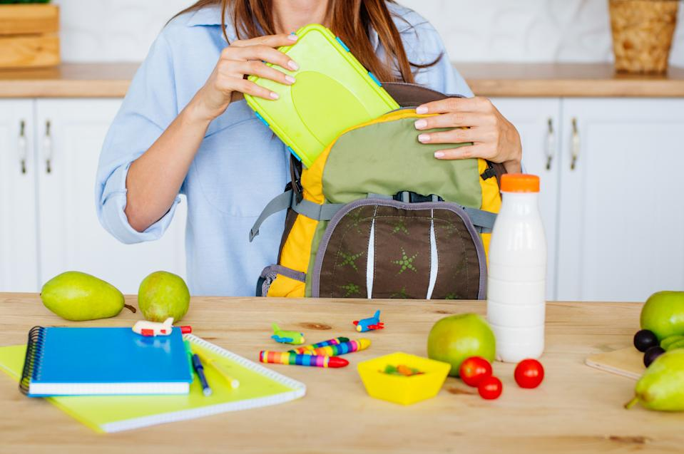 Healthy food concept. Closeup of female hands packing lunch box into a kid's rucksack in the kitchen. Selective focus.