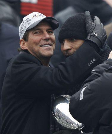 Super Bowl XLVII champion Baltimore Ravens owner Steve Bisciotti (L) hugs retiring Ravens' linebacker Ray Lewis (R) at a team and fan rally in Baltimore February 5, 2013. The Ravens defeated the San Francisco 49ers to win the NFL championship. Lewis holds the Vince Lombardi Championship Trophy. REUTERS/Gary Cameron