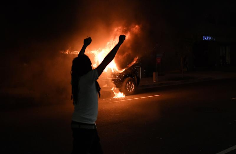 """A demonstrator raises his fists while walking by a burning car outside of the White House on May 30, 2020 in Washington DC, during a protest over the death of George Floyd, an unarmed black man, who died after a Minneapolis police officer kneeled on his neck for several minutes. - Clashes broke out and major cities imposed curfews as America began another night of unrest Saturday with angry demonstrators ignoring warnings from President Donald Trump that his government would stop violent protests over police brutality """"cold."""" (Photo by Eric BARADAT / AFP) (Photo by ERIC BARADAT/AFP via Getty Images)"""