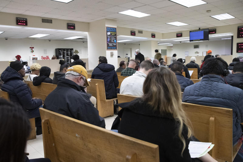 FILE - In this Dec. 16, 2019, file photo, people wait to be served in a Department of Motor Vehicles office in New York. New York Gov. Andrew Cuomo told reporters Wednesday, Feb. 26, 2020, that President Donald Trump is punishing blue states, including New York, over their politics as the president runs for re-election. Among the policies in New York the Trump Administration are unhappy with are a new state law allowing undocumented immigrants to obtain driver's licenses and barring federal officials from accessing the state motor vehicle database. (AP Photo/Mark Lennihan, File)