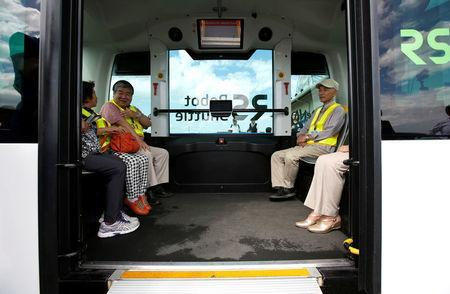 Local residents are seen inside Robot Shuttle, a driver-less, self driving bus, developed by Japan's internet commerce and mobile games provider DeNA Co., during an experimental trial with a self-driving bus in a community in Nishikata town, Tochigi Prefecture, Japan September 8, 2017. REUTERS/Issei Kato