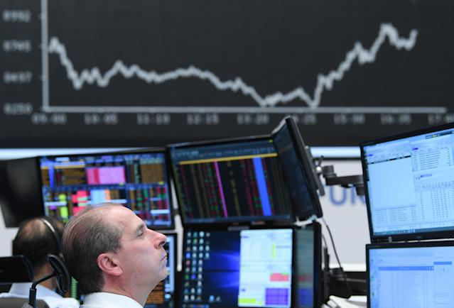 A stock trader sits in front of monitors at the Frankfurt Stock Exchange (Arne Dedert/Picture Alliance via Getty Images)