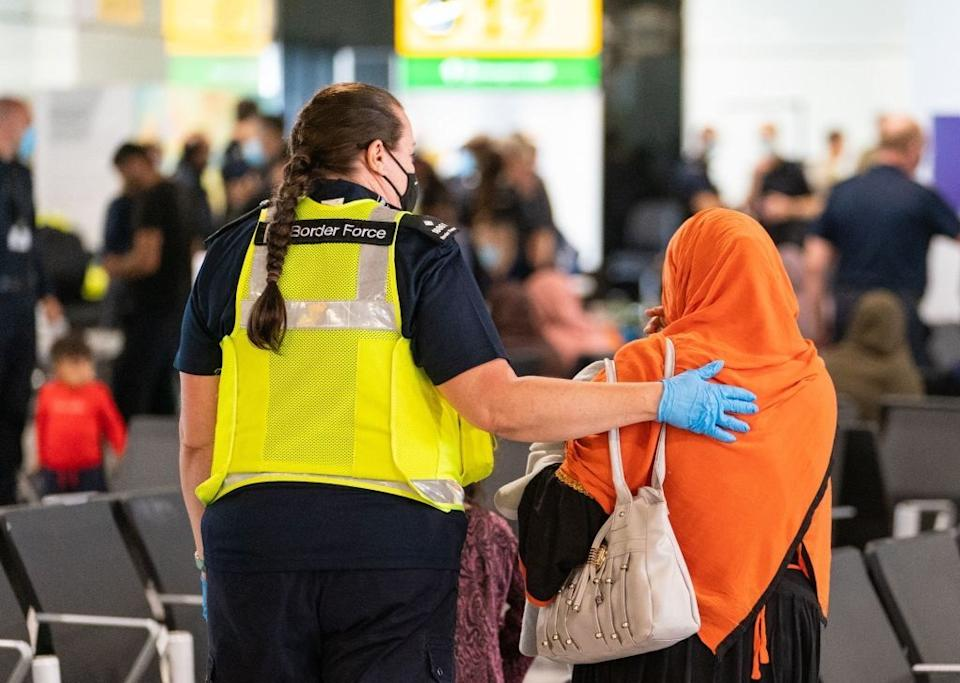 A member of Border Force staff (L) assists an Afghan refugee on her arrival on an evacuation flight from Afghanistan, at Heathrow Airport, London on August 26, 2021. - A terrorist threat against Kabul airport is